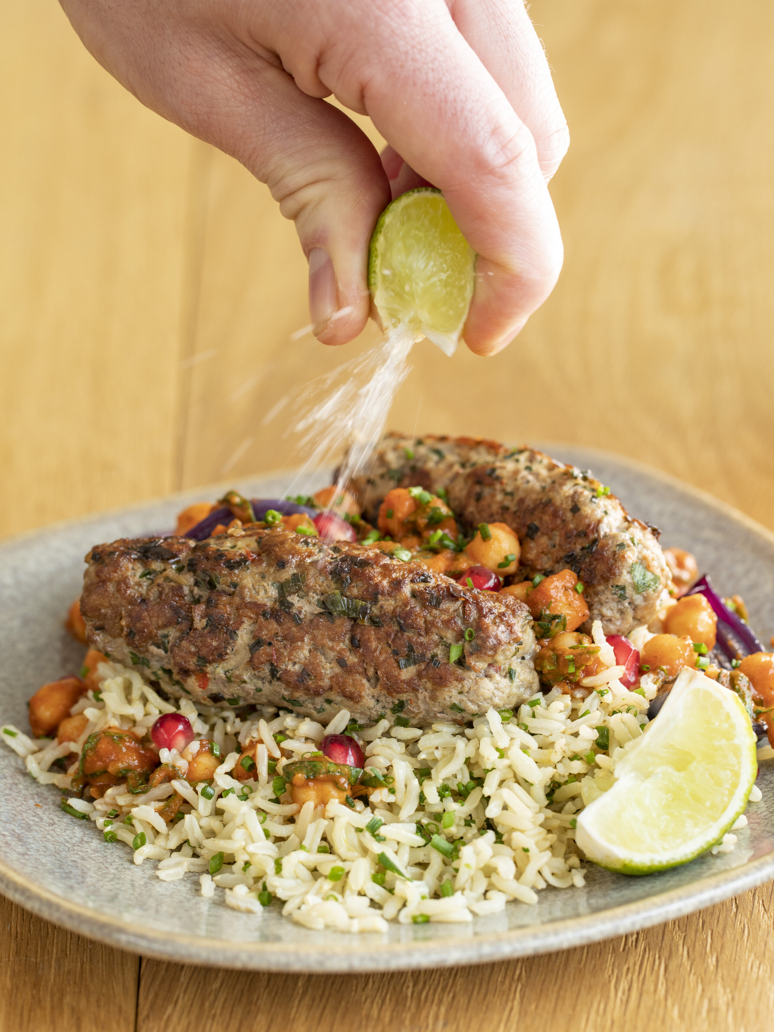 Lean sausages with chickpeas, rice, pomegranate and lime