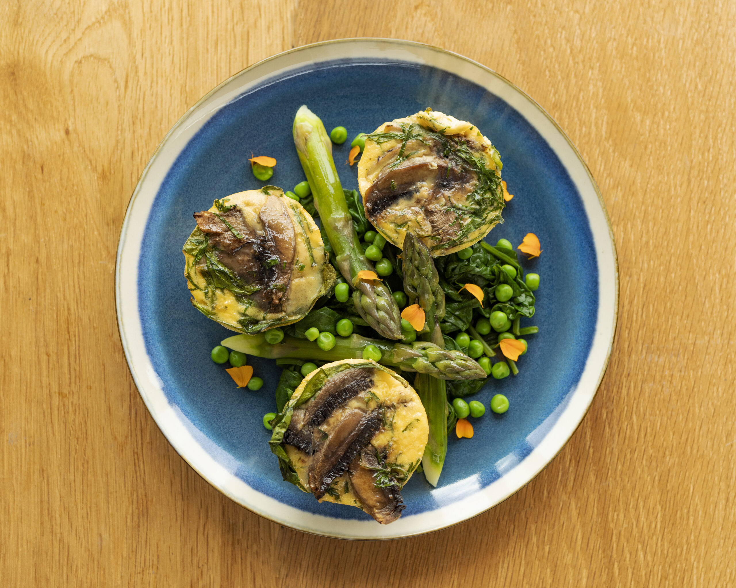 Diet egg muffins with mushrooms, asparagus, spinach and peas
