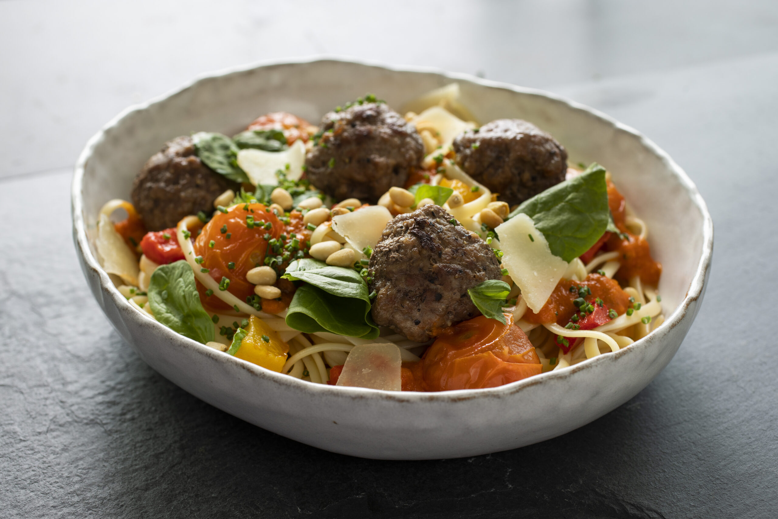 Meat ball linguini with pine nuts, peppers and cherry tomatoes